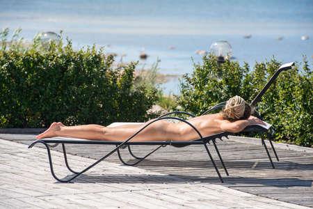Beautiful woman sunbathing on sunbed. Enjoying summer time 版權商用圖片