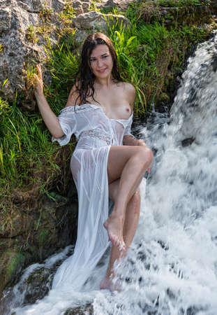 Beautiful young seminude woman in white transperent  dress enjoying summertime in waterfall