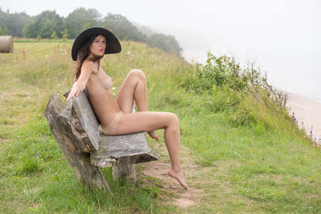 Young nude woman in black hat sitting on a wooden bench at the beach