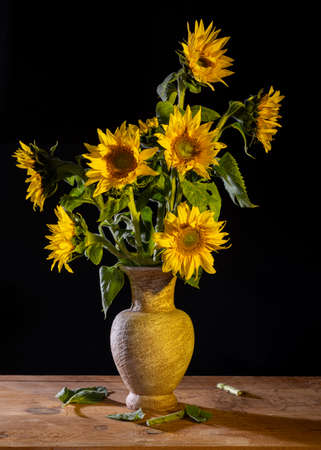 Beautiful bouquet of sunflowers in vase on a wooden table. Autumn still life