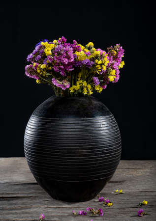 Beautiful bouquet of limonium in vase on a wooden table. Still life