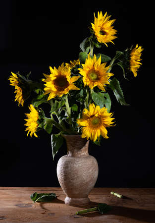 Beautiful bouquet of sunflowers in vase on a wooden table. Autumn still life 免版税图像