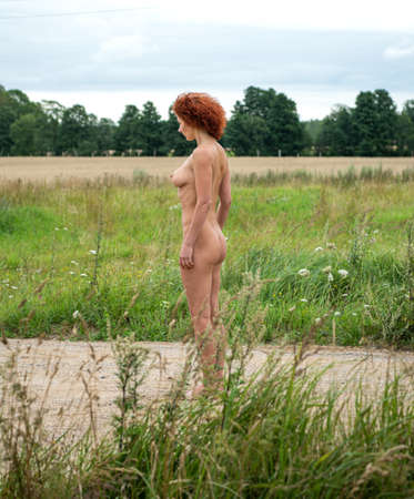 Young nude woman posing on nature background. Sexy naked enjoying summer time 免版税图像