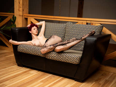 Gorgeous naked  posing indoors. Sexy nude woman relaxing on sofa