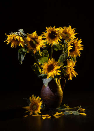 Beautiful bouquet of sunflowers in vase on a black table over black background. Autumn still life Foto de archivo