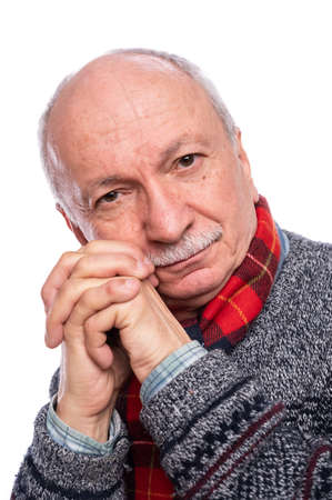 Thoughtful senior man posing in studio over white background