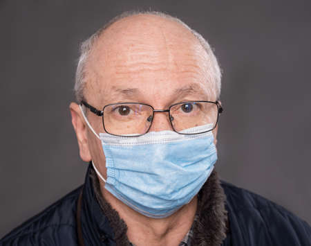 Health care concept. Senior man in protective mask  posing in studio over gray background 免版税图像