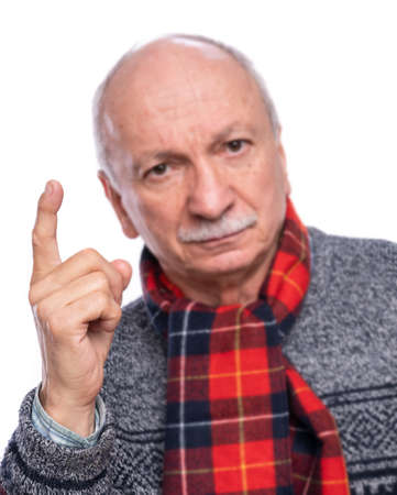 Serious man raising forefinger in warning gesture over white background