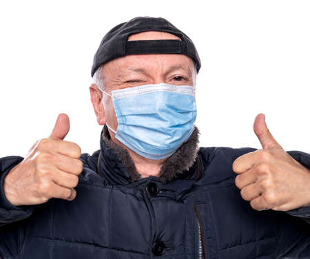 Health care concept. Senior man in protective mask  posing in studio over white background. Gesturing OK sign 免版税图像