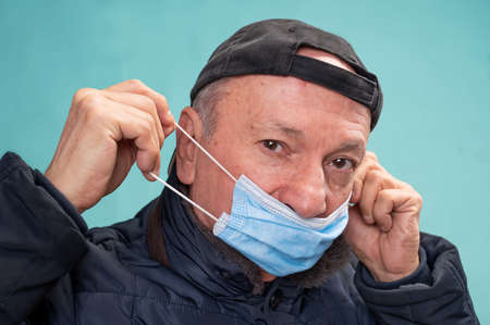 Health care concept. Senior man wearing  protective mask  over blue background