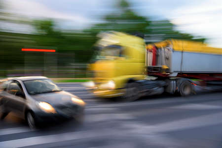 Dangerous city traffic situation between a car and a truck in motion blur. Defocused image