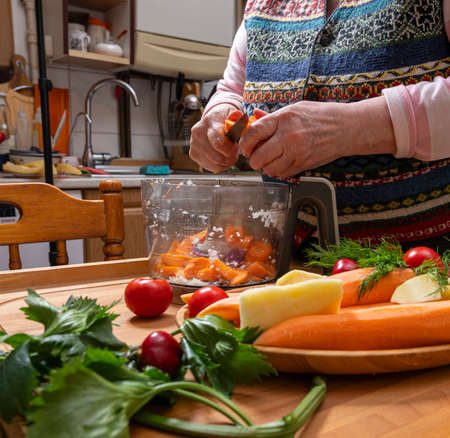 Food and healthy eating concept. Woman chops vegetables in a food processor for s sauce