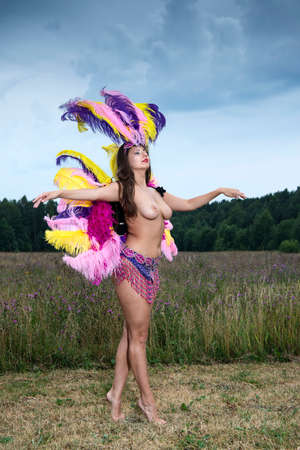 Young naked woman in bright colorful carnival costume posing outdoors. Sexy brunette preparing for carnaval Stok Fotoğraf