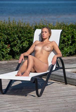 Beautiful woman sunbathing on sunbed near swimming pool. Sexy blonde enjoying summer time