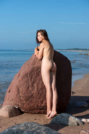 Young beautiful woman posing near stone at the beach. Sexy brunette outdoors Stockfoto