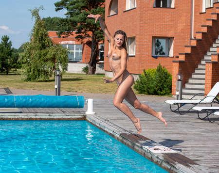 Beautiful young woman enjoying summer time near the swimming pool