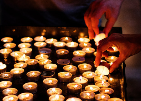 Woman hand lighting candles in a church with another hand blurred in the background Stock Photo