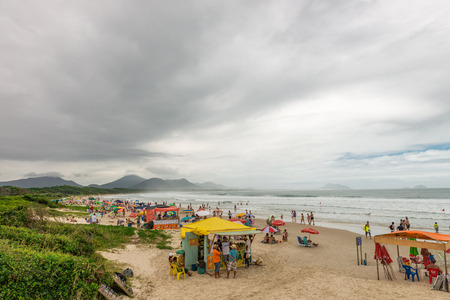 tent city: Florianopolis, Brazil - Jan 8, 2016:  A lot of people at the Barra beach enjoying a holiday in Florianopolis -SC, Brazil.