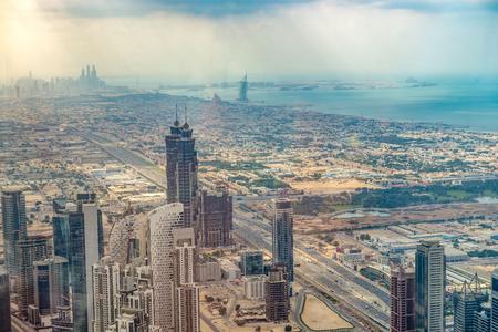 aerial view: Dubai, United Arab Emirates - Dec 2, 2014: Aerial shot of Dubai including the Burj Al Arab hotel, a luxury 7 stars hotel built on an artificial island. Photo taken at the Burj Khalifa observation deck