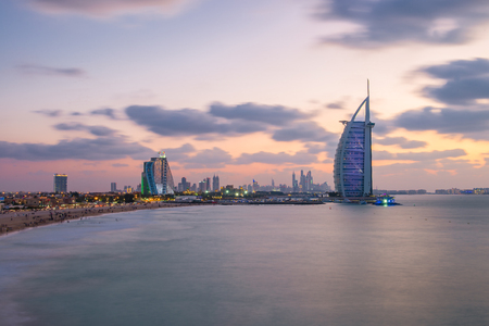 View of the illuminated Burj Al Arab and Jumeirah Beach Hotel at the sunset. View from the Jumeirah beach opposite side, Dubai. Burj Al Arab is a luxury 7 stars hotel built on an artificial island.