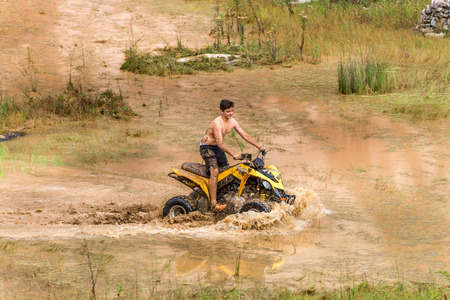 off road biking: Minas Gerais, Brasil, Dec,27 - 2015: Man in nature go off road on a quad bike rally over mud puddle in countryside.