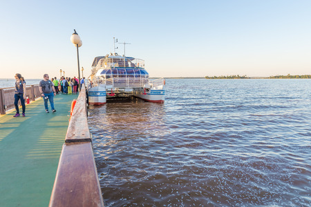 joyride: Foz do Iguacu, Brazil - july 10, 2016: Tourist ship boarding people and getting ready for a tour over the parana river in Itaipu dam park at the brazilian border.