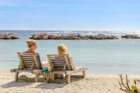Curacao, Caribbean - September 29, 2012: Two girls got themselves in a front row seats at mambo beach in Curacao.