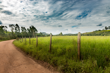 vanishing point: Dirt Road and barbed wire fence on summer afternoon in Minas Gerais Mountains, Brazil Stock Photo