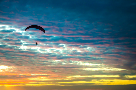 Motorized paraglider flying up high on the sky by the sunset