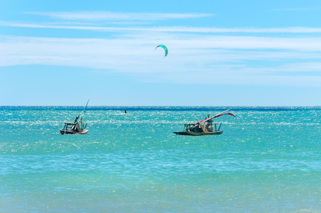 Jangada boat and kite surfers sailing together on the sea in Cumbuco, Brazil