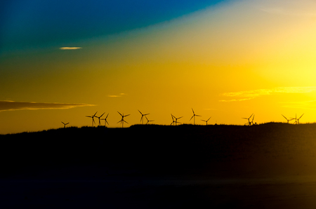 Landscape with windmills farm for clean energy at the sunset
