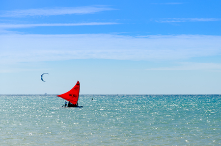 Cumbuco, Brazil, jul 9, 2017: Jangada boat and kite surfers sailing together on the sea in Cumbuco, Brazil