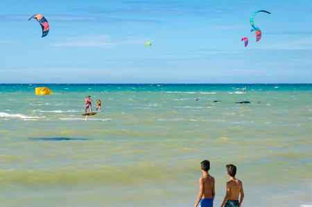 Cumbuco, Brazil, jul 9, 2017: Kids observing kite surfer equipment on the sea in Cumbuco