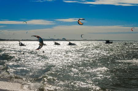 Cumbuco, Brazil, jul 9, 2017: The sunset with kite surfers enjoying the sea at evening