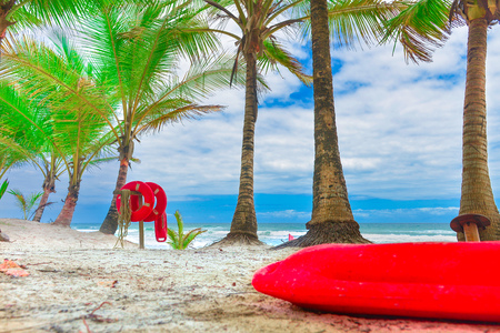 Red life buoy with rope and a flag on the background Stock Photo