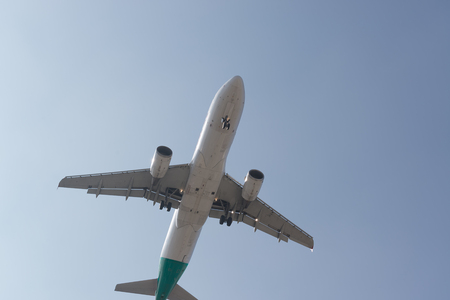 Airplane flying up high and departing from the airport Stock Photo