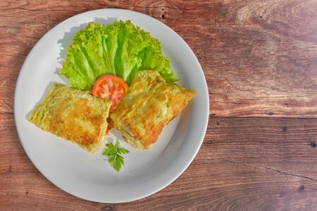 Rich omelet stuffed with melted cheese with side salad. Wood background Stockfoto