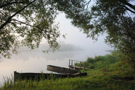 Sunrise, boats at coast in a morning fog. photo