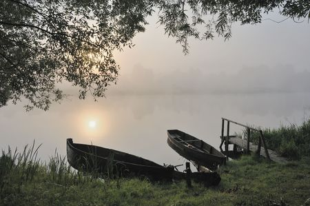 The sun, boats at coast in a morning fog rises. photo