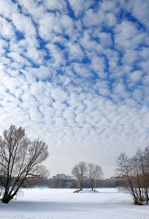 The winter sky with small frequent clouds over lake in a city. Stock Photo - 5670564
