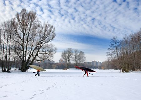 Two oarsmen with oars and kayaks go on ice of the frozen lake. Stock Photo - 5670580