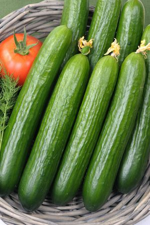 Smooth cucumbers in a basket with a tomato. Stock Photo