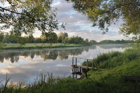 Dawn on the river Vilija, Belarus. The sky with clouds, the first rays of the sun.