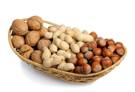 Walnuts, hazelnuts and peanuts in a wicker basket on a white background, isolated photo