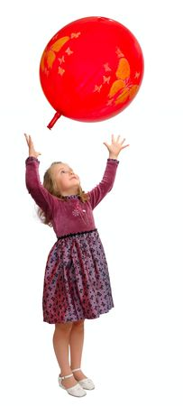 Girl in a smart dress plays with a red balloon. photo