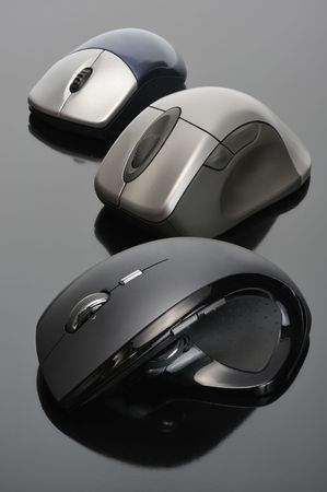 Modern wireless computer mouses on black background photo