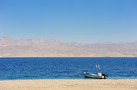 Gulf of Eilat Red Sea, the boat on the shore and Jordanian mountains in the background. photo