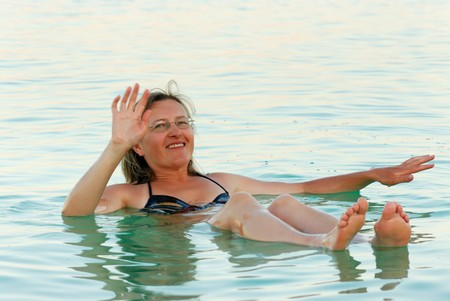 The woman lies on the water from the Dead Sea photo