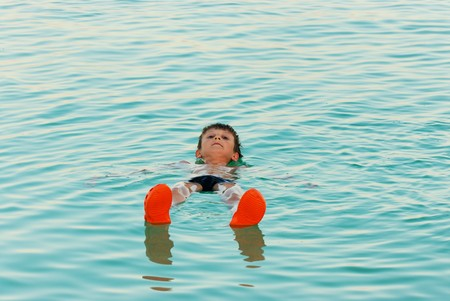 The boy lies on the water from the Dead Sea photo