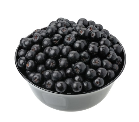 Aronia berries in a black cup on a white background, isolated Stock Photo